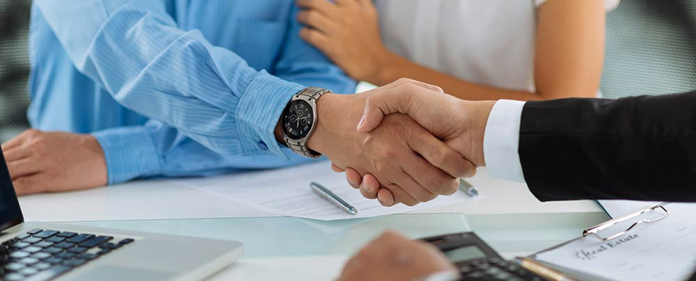 Business professional shaking hands with two home buyers.